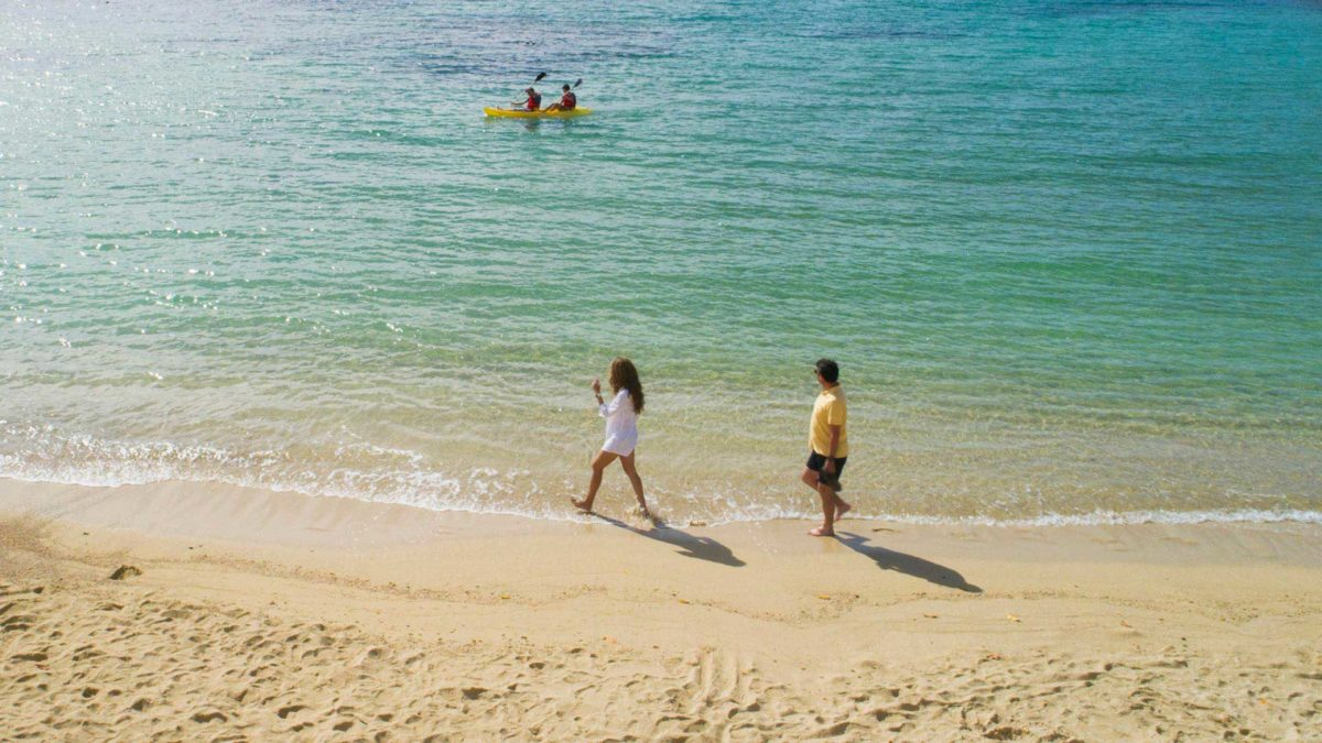 Couple strolling down Garrapatero Beach in the Galapagos Islands