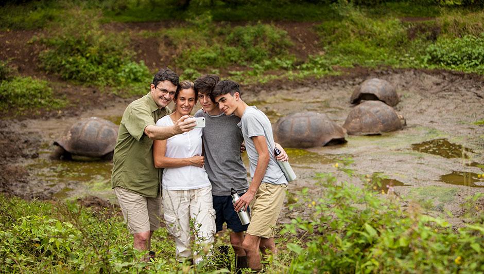 Familia posando junto a Tortugas Gigantes de Galápagos en las Tierras altas de la Isla Santa Cruz